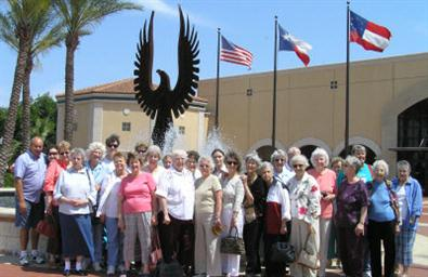 A group of senior citizens standing outside the Senior Services Center near a flag pole