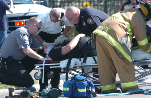 Paramedics and firefighters giving medical attention to someone on a stretcher