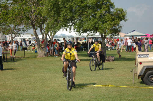 2 bike medics riding bikes on the grass at the festival