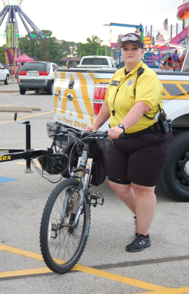 A bike medic in a yellow shirt and black shorts with her bicycle at the festival