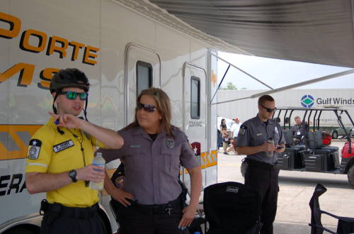 A bike medic with a helmet and sunglasses on talking to a uniformed EMT at the festival