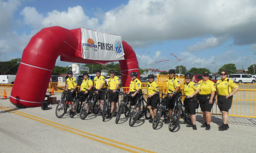 Uniformed EMTs with yellow shirts and black shorts with bikes in front of a red finish line
