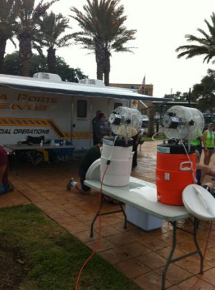 Water coolers and fans set up on a table outside the EMS van at the half marathon
