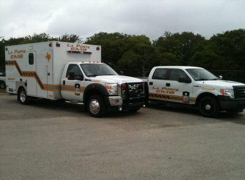 A white ambulance and a white EMS pick up truck