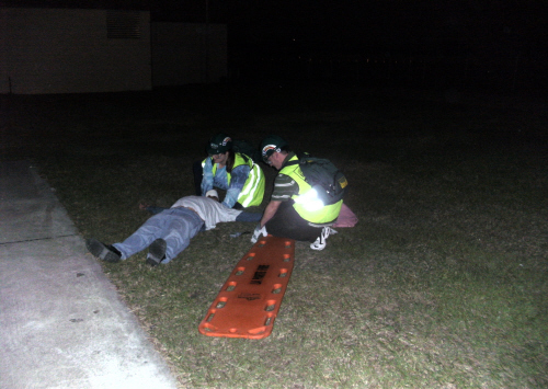 2 people in green safety vests at night in the grass and a man laying down next to an orange medical transport board
