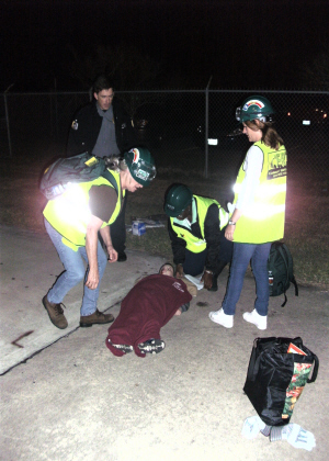 A group of people in green safety vests at night helping a person laying on the ground