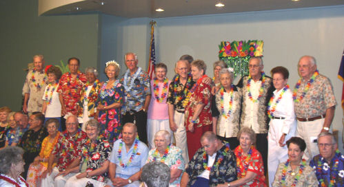 A large group of senior citizens participating in a hawaiian-themed vow renewal ceremony