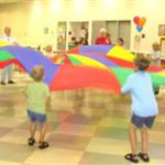 A group of children and senior citizens participating in a recreational activity using a large parachute