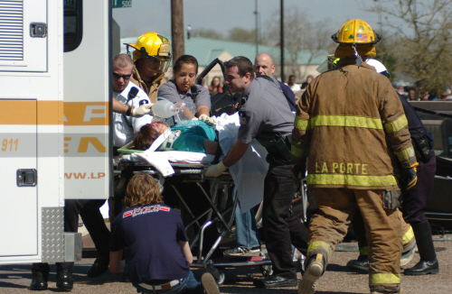 Paramedics and firefighters giving emergency medical attention to someone on a stretcher