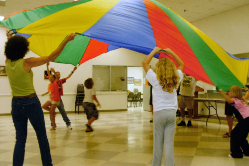 A group of children participating in a recreational class using a large parachute